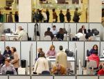 Varios funcionarios de la Agencia Tributaria atienden a ciudadanos en una de sus oficinas en Madrid. (f. alvarado / EFE)