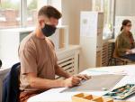 Dos trabajadores en la oficina con mascarilla y manteniendo la distancia de seguridad.