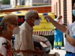 Un sanitario toma la temperatura a un hombre antes de acceder este miércoles al Centro de Salud de Los Ángeles, en el distrito de Villaverde, donde el gobierno regional ha puesto en marcha uno de los dispositivos de pruebas PCR