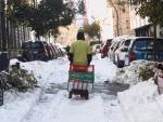 Un hombre arrastra una carretilla por una calle del centro aún con nieve y árboles caídos en Madrid (España), a 13 de enero de 2021