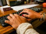 Unas manos de mujer escriben en el teclado de un ordenador, sobre una mesa de madera.