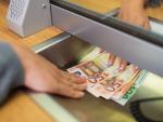 Fotografía de una entrega de dinero en un banco. El acceso al dinero de la cuenta bancaria de un fallecido depende de varios factores.