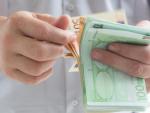 Fotografía de un jubilado con el dinero de su pensión. Se pueden compatibilizar dos pensiones si se trabajó como autónomo y asalariado.