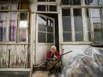 Una anciana sostiene un arma en la puerta de su casa en la localidad e Stepanakert, en pleno conflicto de Nagorno Karabaj