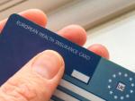 Viajero sosteniendo la tarjeta sanitaria europea.
