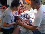 Integrantes del Open Arms atienden a una migrante rescatada