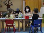 Una profesora atiende a dos niños en el regreso antes de las vacaciones del verano de algunas actividades de Infantill