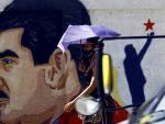 Una mujer camina bajo su paraguas frente a un mural con la imagen del presidente de Venezuela, Nicolás Maduro