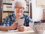 Pensionista usando el móvil en su cocina.
