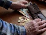 Fotografía de un jubilado contando el dinero de su pensión.