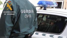 Un agente de la Guardia Civil junto a un coche patrulla. GUARDIA CIVIL 4/2/2021