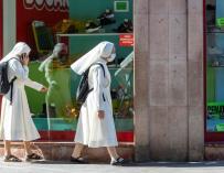 Dos monjas pasan por delante de un comercio en Zaragoza.