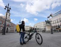 Un repartidor de Glovo descansa en la Puerta del Sol en pleno confinamiento.