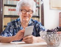 Mujer mayor pensionista usando el móvil.