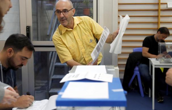 Un funcionario de Correos entrega el voto emitido por correo en la Escuela Mireia de Barcelona. /EFE/Toni Albir