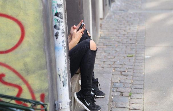 Fotografía de una niña adolescente con su móvil.