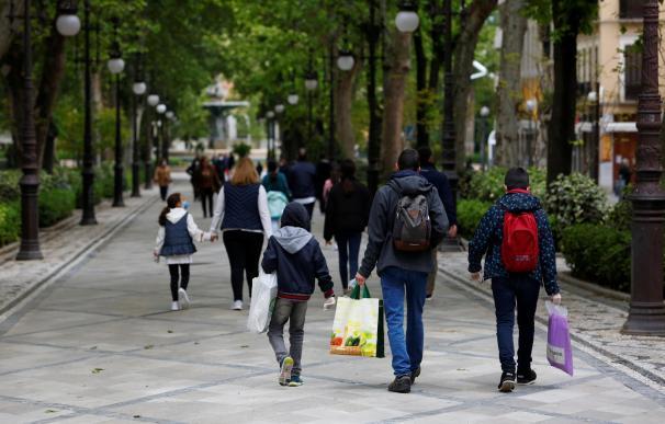 Varios padres y sus niños pasean por las calles de Granada