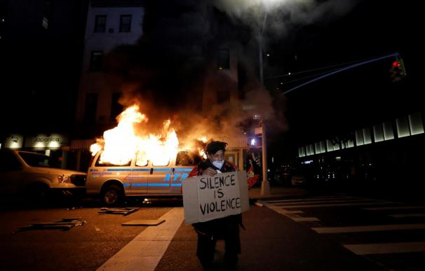 Un manifestante muestra una pancarta mientras arde una furgoneta de la Policía de Nueva York a su espalda