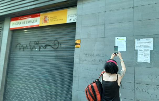 Una ciudadana fotografía los carteles informativos colocados en la puerta de las oficinas de empleo aún cerradas.