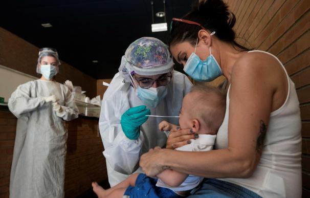 Una sanitaria realiza un test PCR a un niño en un espacio habilitado fuera de un Centro de Salud de la ciudad de Zaragoza.