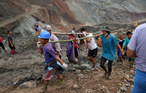 Voluntarios llevan el cuerpo de una víctima después de un deslizamiento de tierra en una mina de jade en Hpakant, Birmania