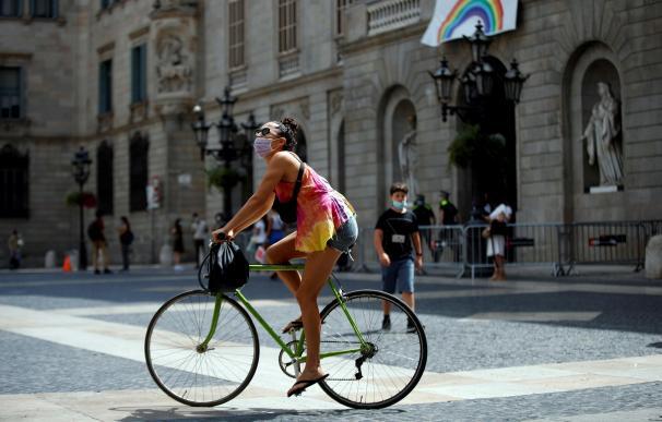 Una joven pasea con su bicleta , protegida con su mascarilla, este jueves, primer día en que es obligatorio el uso de mascarillas en toda Cataluña aunque se puedan guardar las distancias.