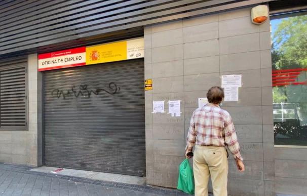 Un ciudadano observa los carteles informativos ante una oficina cerrada de empleo.