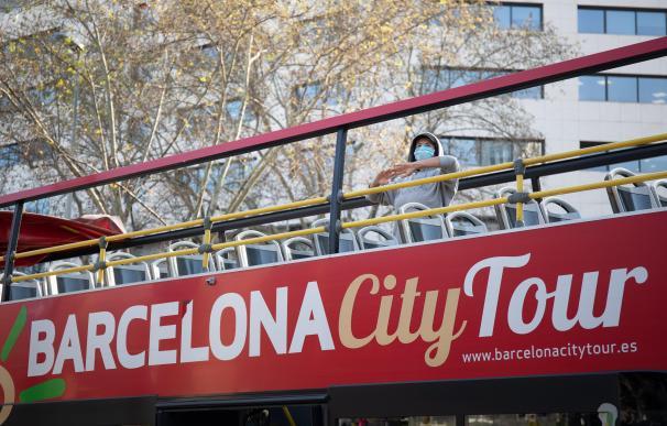 Un turista solitario observa desde el techo de un autobús panorámico en Barcelona,