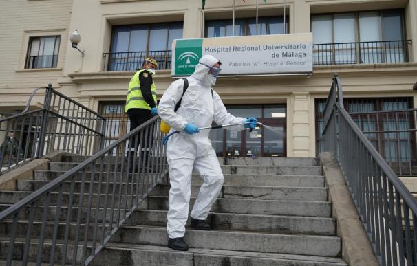Dos efectivos de las Fuerzas Armadas realizan trabajos de desinfección ante un centro sanitario en Málaga.