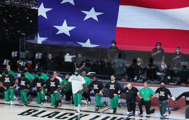 Varios jugadores de los Boston Celtics se arrodillan para protestar contra el racismo antes de comenzar un partido.