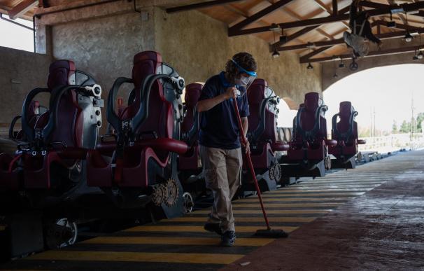 Un trabajador con mascarilla limpia unas vacías instalaciones de un parque de atracciones.