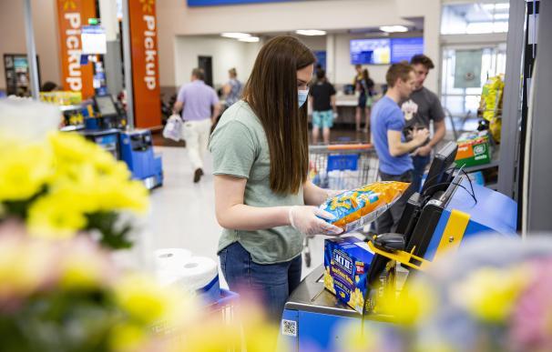 Una joven utiliza uno de los sistemas para cobrarse por sí mismo recién instalados en Walmart.