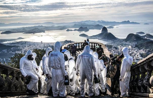 Varios militares con trajes protectores se disponen a desinfectar el Cristo Redentor de Río de Janeiro.