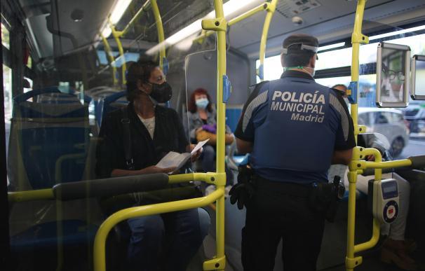 Un agente de la Policía Municipal de Madrid realiza un control de movilidad en una línea de autobús que pasar por el distrito de Puente de Vallecas, Madrid.