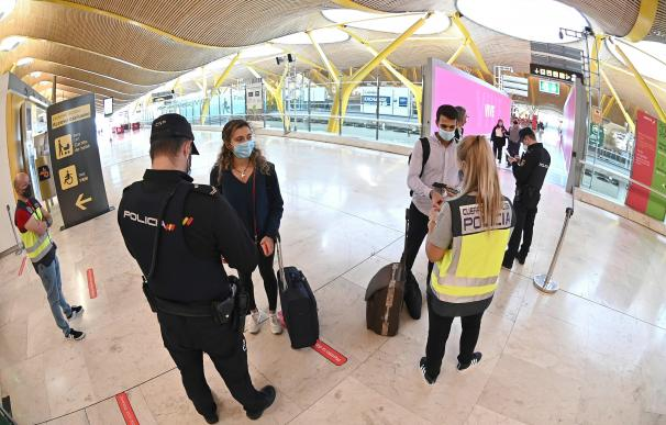 Agentes de la Policía Nacional controlan el acceso a la T-4 del Aeropuerto Adolfo Suárez Madrid-Barajas, hoy viernes, para vigilar el cumplimiento de las restricciones a la movilidad impuestas por el estado de alarma.