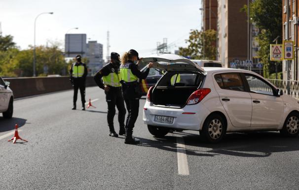 Varios agentes de Policía Nacional inspeccionan un vehículo en un control en la carretera A-5, en Madrid.