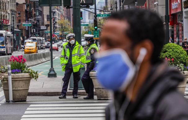 Un ciudadano con mascarilla pasa por delante de varios policías en Nueva York.