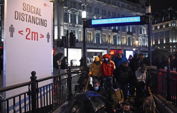 Varios ciudadanos entran en una estación de Metro en Londres, tras elevarse las restricciones.