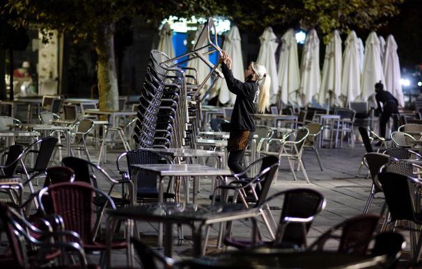 Una camarera recoge la terraza de un bar en Valladolid momentos antes del inicio del toque de queda impuesto por la Junta de Castilla y León debido al alto número de contagios de coronavirus en la Comunidad. EFE/NACHO GALLEGO
