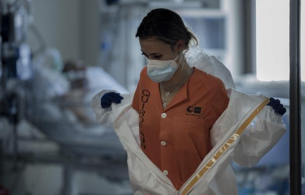 Una sanitaria se quita el traje de proteccion en la UCI del Hospital Universitario Ramón y Cajal