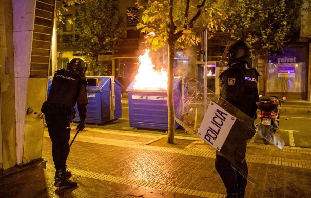 La policía, junto a un contenedor de papel ardiendo durante los nuevos incidentes registrados el domingo en Logroño.