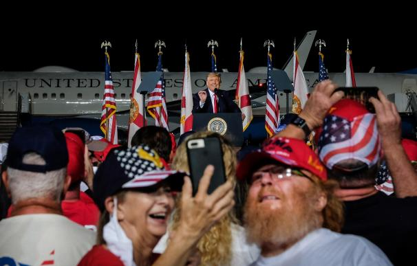 Dos asistentes se toman una fotografía durante el discurso del presidente estadounidense, Donald Trump (C), en un acto de campaña en Pensacola, Florida.
