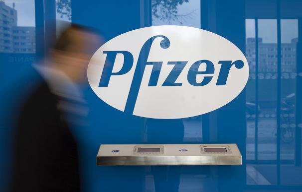 Un hombre camina ante el logo de Pfizer, en Berlín.
