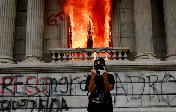 Un manifestante desafía a la policía a la puerta del Congreso en llamas de Guatemala.