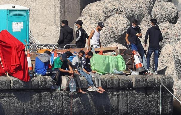 Varios inmigrantes magrebíes este jueves en el muelle de Arguineguín, en el que bajan las garrafas de agua hasta el mar con una cuerda para mantenerlas frescas.