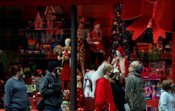 Un grupo de turistas pasa por delante del escaparate navideño de Macy's en una ciudad inusualmente vacía.