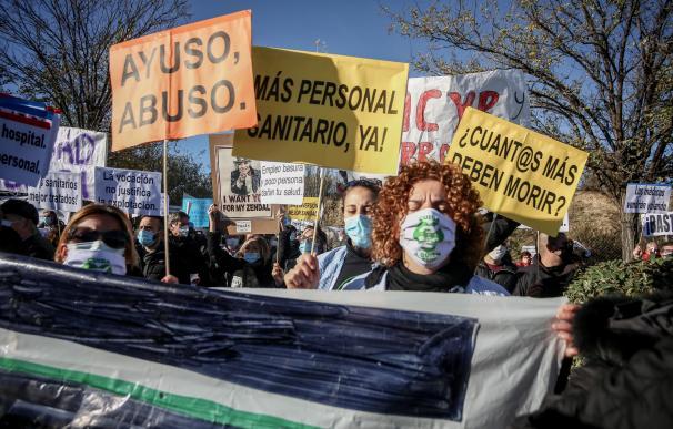 Varias personas se manifiestan con pancartas durante una concentración convocada por la plataforma Sanitarios Necesarios en la puerta del Hospital Enfermera Isabel Zendal.