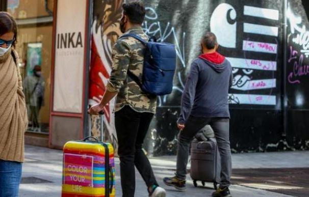 Madrid jóvenes paseando coronavirus mascarillas maleta