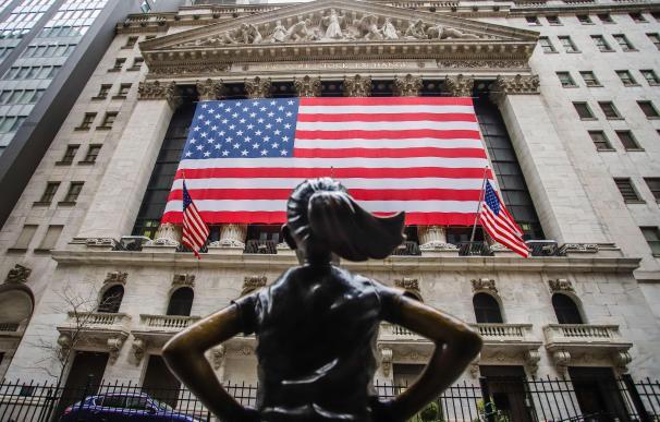 Fachada del New York Stock Exchange adornada con una bandera gigante de Estados Unidos.