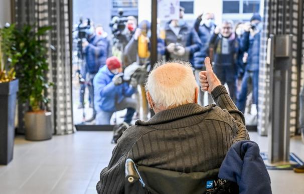 Un anciano saluda a los medios que se agolpan en la puerta para captar la vacunación.